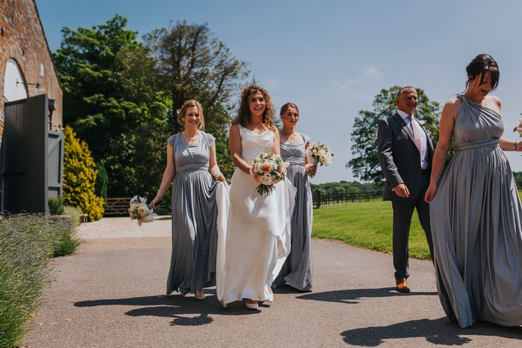 The mix and match style of these grey bridesmaid dresses complement the bride's dress perfectly. Photo by Benjamin Stuart Photography #weddingphotography #bridesmaids #weddingday #herecomesthebride #weddingparty