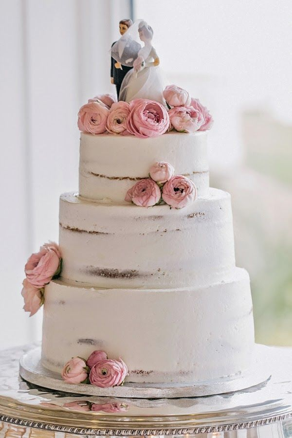 delicately messy three-tiered cake with pink ranunculus and a classic cake topper