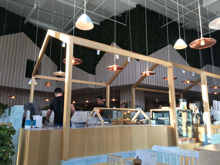 The interior of this cafe has used a raw finished light timber in both furniture and cladding to break up and create intimacy in a large open space. Keeping the timber raw and light gives it a soft presence that contrasts against the sharp linear lines of of the structures themselves.