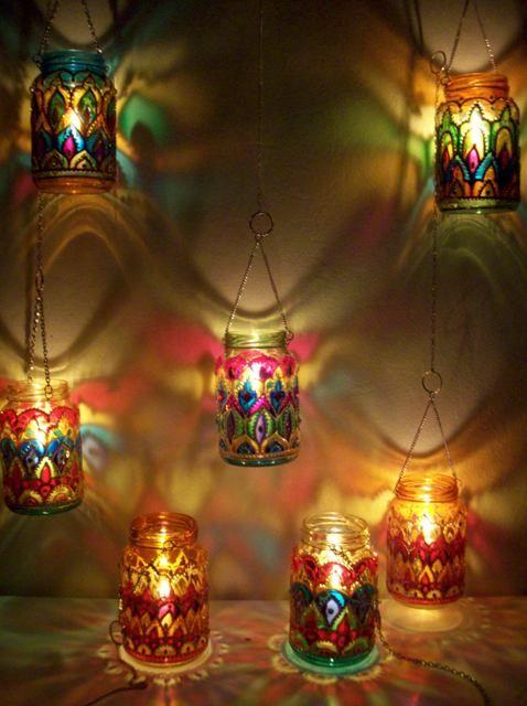 Estas lamparinas feitas com vidros reciclados, ganharam ainda mais charme com estas correntinhas que foram usadas para suspendê-las. Os vidros foram pintados a mão com tinta em alto relevo. A artesã caprichou na iluminação usando velas aromáticas e cores vibrantes, o resultado são estas românticas lamparinas que exibem efeitos maravilhoso quando acesas.