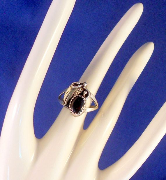 Very nice Navajo handmade ring with onyx. The ring features lovely applique work showing a leaf, tendrils, and a raindrop which symbolize life, growth, and prosperity. All done in sterling silver. The ring is size 5.75. The top of the ring measures 5/8 long. Signed on the back JR and STERLING. Condition is very good. Shipped in a small box perfect for gift giving.  International Ring Size Conversion Chart: http://www.ringsizes.co  The item photographed is the exact one you will...