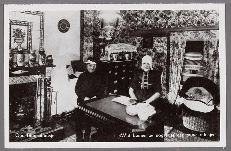Spakenburgs interieur met een man en vrouw in dracht zittend achter de tafel. Links een betegelde schouw en op de achtergrond een pronkbedstee, een wieg en wandborden. 1930-1955 't Blokhuiswapen #Utrecht #Spakenburg