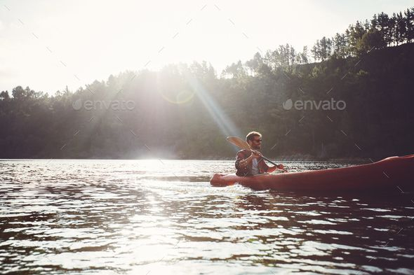 Man paddling kayak on a summer day by jacoblund. Young man canoeing in a lake. Man paddling kayak on a summer day.