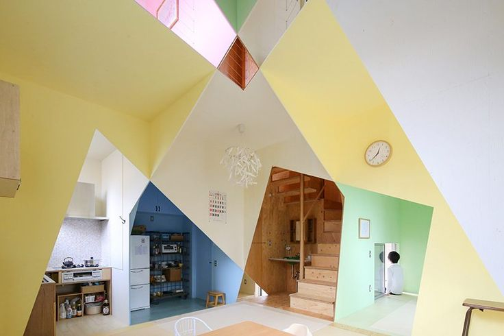 a 'patchwork of rooms' has been created where each angled plywood plane has then been painted in a different color, lending the home an abstract quality.