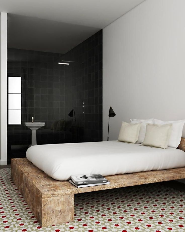 Contemporary bedroom with hydraulic floor tiles and black bathroom tiles