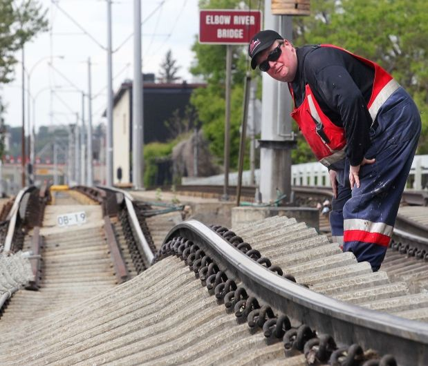 Dean Hagen of Calgary Transit's track and way department surveys the mess of rail lifted and twisted off its bed north of the Stampede Erlton CTrain Station on Sunday. Adjacent Macleod Trail northbound lanes were also destroyed. Photograph by: Ted Rhodes Ted Rhodes, Calgary Herald