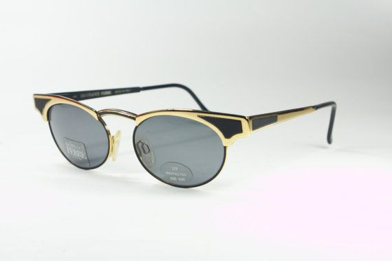 A collectible frame made and designed in the 80s by the revolutionary designer Gianfranco Ferrè. The sunglasses are very close to the model worn by Fergie of the Black Eyed Peas Top quality golden metal frame with matte black details. Sunglasses new and unworn, coming from an 80s deadstock and still labeled.  Overall width 5,6 in 14,3 cm Lenses width 1,95 in 5 cm Arms length 5,15 in 13,2 cm -   Handling time & shipping policy  - Your Items will come in a free pouch bag (original one if av...