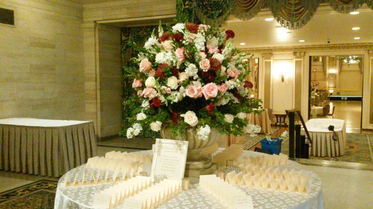 A luxurious arrangement of cascading orchids, blush garden roses, merlot dahlias, and hydrangea for Erika and Mike's escort card table at the Hotel duPont.