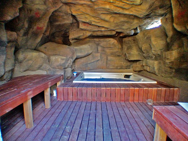 Private Spa chamber, constructed rock cave. Hardwood seating, glass brick natural lighting.