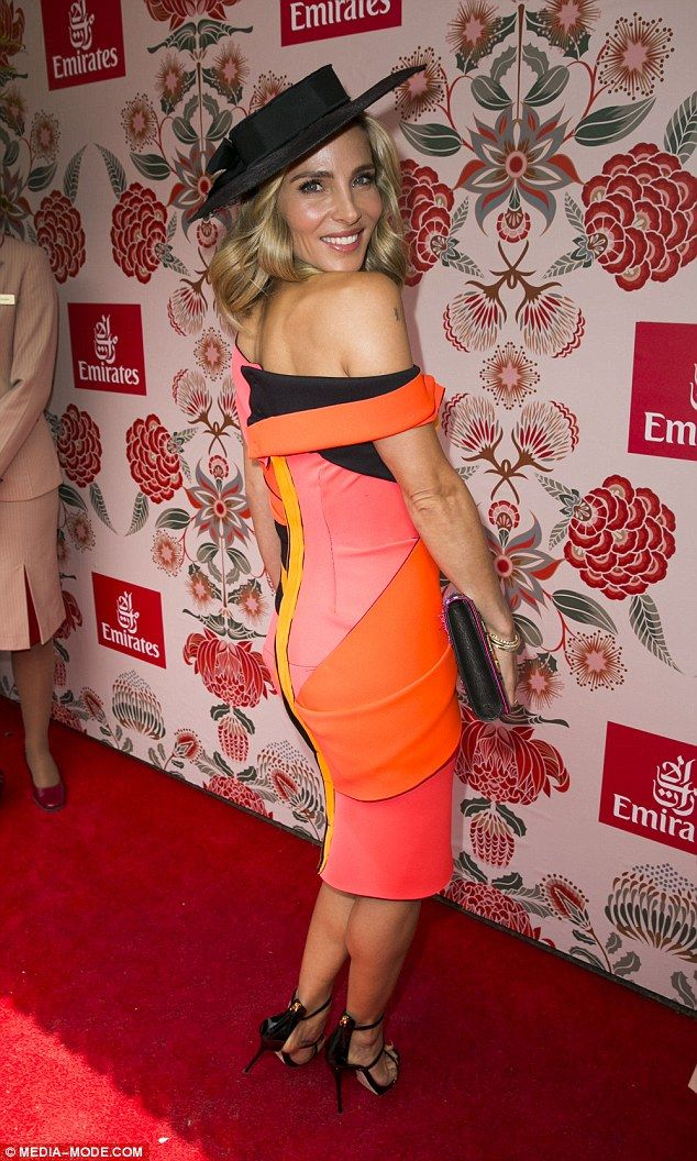Accessorise: The 40-year old teamed the dress with a black hat, matching strappy heels and...