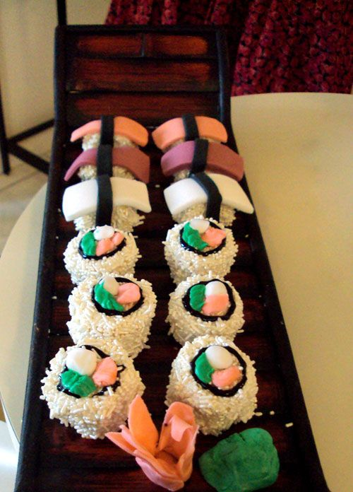 """Sushi"" Cupcakes, genius!     ""We cut the cupcakes in circles, iced them, and rolled them in the long pearlized white sprinkles, then used fondant to make the fish and wasabli and ginger. The sashimi looking ones were the same, just cut in a rectangle.    OBVIOUSLY all presented on a sushi boat. It was fun!"""