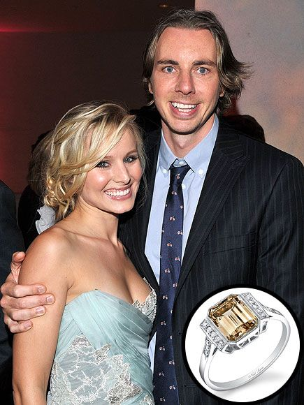 Kristen Bell's engagement ring features a fancy-colored emerald cut diamond, flanked by diamonds.