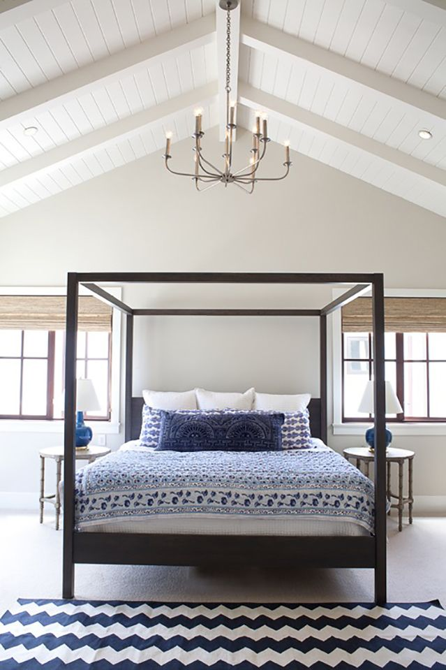Elegant bedroom design with pointed white wood paneled ceilings and four  poster bed