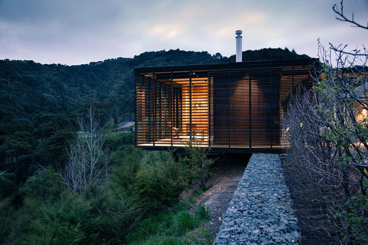 Set atop the New Zealand hills of Clevedon sits a cabin-like timber and steel creation from Herbst Architects.