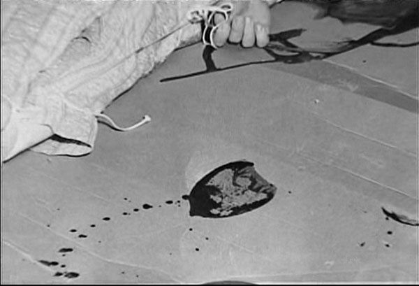 The body of Herb Clutter in the basement of the Clutter home. He had been hanged from an overhead pipe, his throat was slit and he was then shot. After the murder, his body was placed on a mattress on the floor. A boot print left on the floor beside the body would later be matched to boots owned by Perry Smith.
