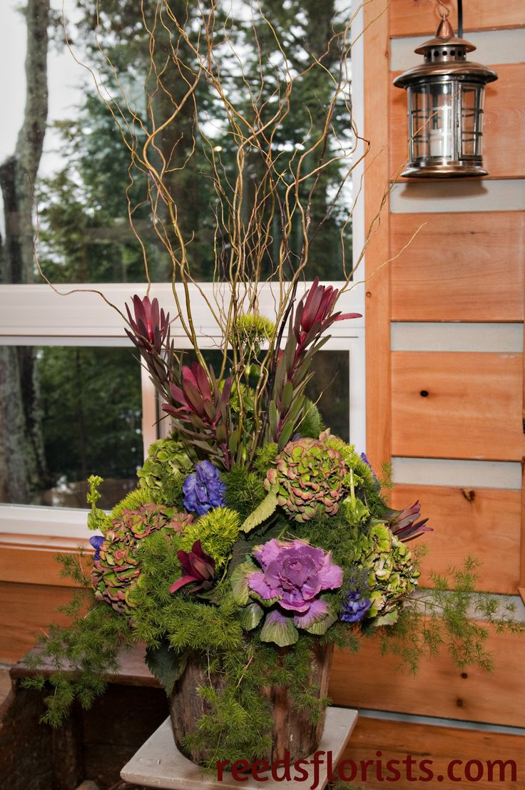 The rustic container echoes the forest just outside the window. Exclusively created by our experienced bridal designers. reedsflorists.com
