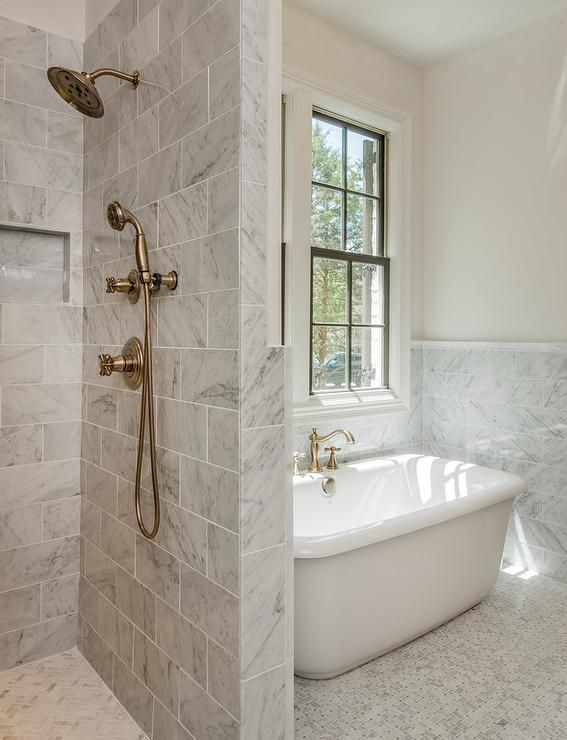 Gray bathroom features a freestanding tub atop a gray marble basketweave tiled floor placed under windows next to a walk-in shower clad in gray marble alongside a white herringbone tiled shower floor.