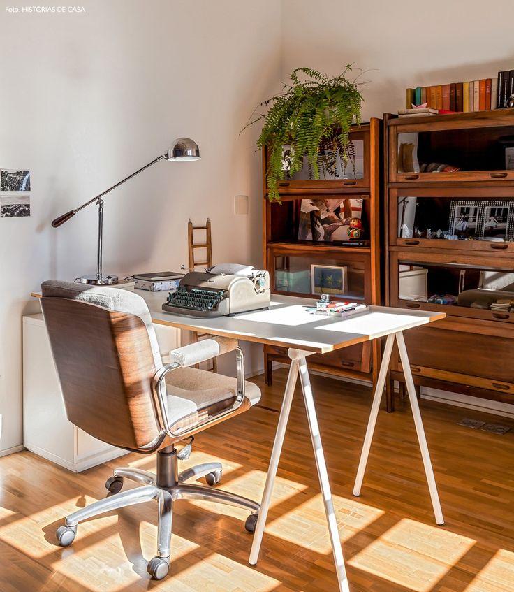 Home office com mesa de cavalete e armários de madeira.