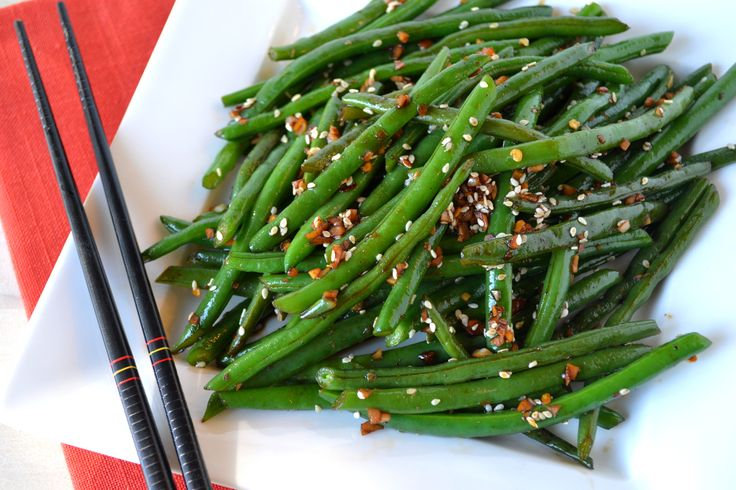 1 lb green beans; 2T fresh grated ginger; 2T thinly sliced garlic; 1T sesame oil; 1/4 C water 2T soy sauce; 1T rice vinegar; 2T chili flakes; 1T sesame seed Rinse and trim green beans Mix sauces Boil green beans3-5 min in wok until crispy tender. Remove/drain. Heat oil over high heat, stir in ginger and garlic until aromatic, combine green bean, stir constantly until beans are soft about 2-3 minutes. Combine sauce mixture, stir around until the sauce is thicken and glazes the bean.