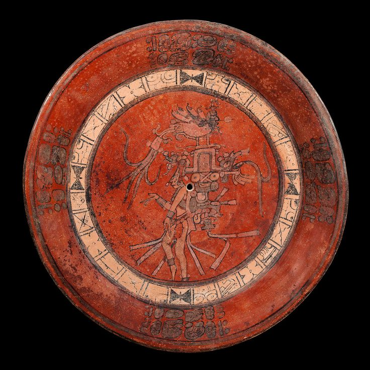 View 1: Large Plate Decorated with a Scene of the Maize God, Maya - Mexico - Predominantly painted in orange tones, the interior surface of this large Late Classic period plate is decorated with a Maize god scene. The latter is surrounded by a light cream-colored skyband and several glyphic texts on the flaring sidewall.