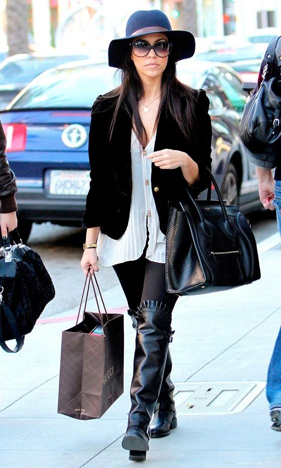 Kourtney Kardashian's Wearing A Black, Floppy Hat: A White, Loose, Blouse: On Top, A Black Blazer: Black Leggings: And Black, Knee-High Boots. Gotta Love Her Style!
