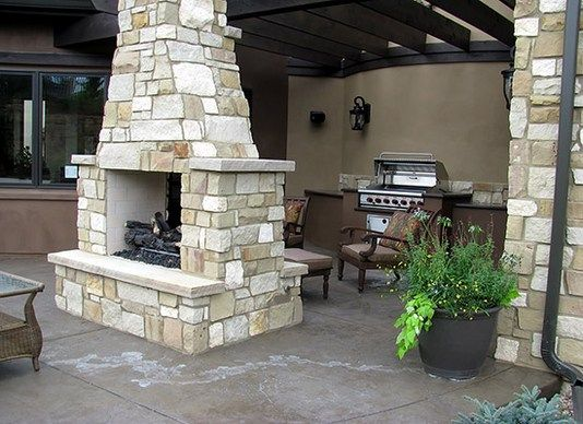 Outdoor grill with see through fireplace and pergola attached to house