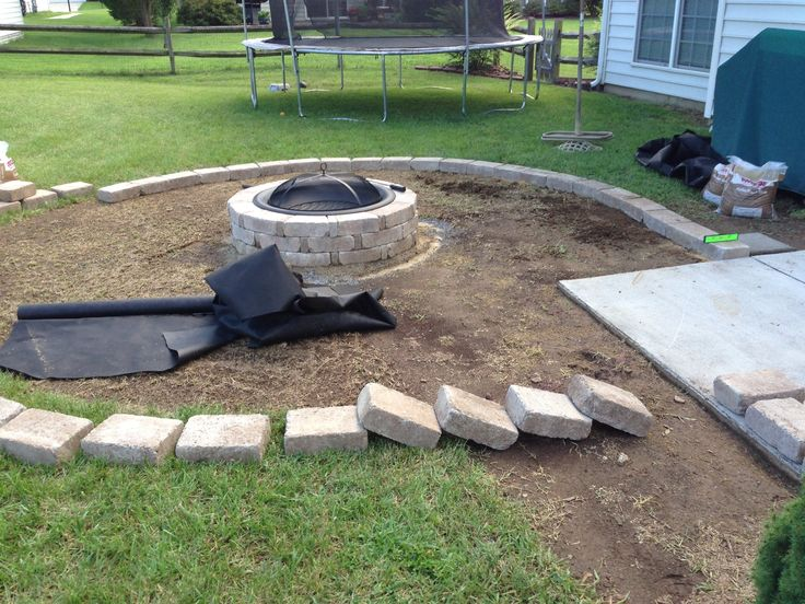 Laying the rumble stone border for fire pit backyard