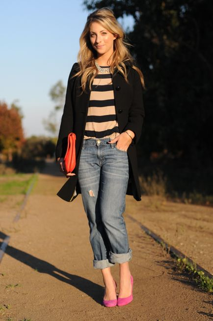 A striped shirt, with a big necklace, and a black trench coat, boyfriend jeans, with a bright orange clutch and bright pink heels.