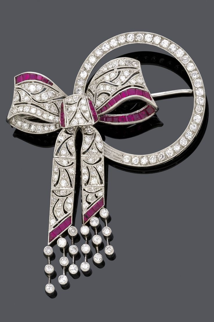 A BELLE EPOQUE RUBY AND DIAMOND BROOCH, CIRCA 1910. Designed as a circle with an openwork bow, set with single-cut diamonds and carré-cut rubies, mounted in platinum. Length 6.3cm. #BelleÉpoque #brooch