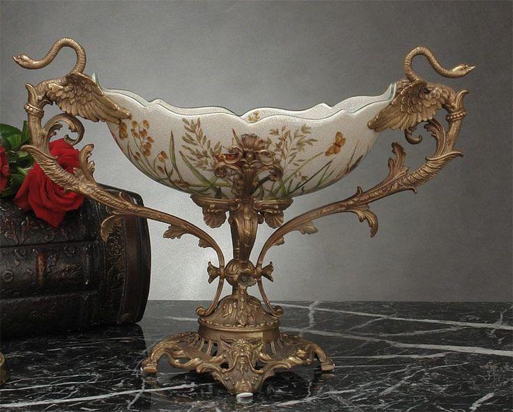 Niebywała forma, subtelna ornamentyka polnych kwiatów i motylków, elegancka kolorystka porcelany o krakelurowym szkliwie oraz niezwykłe uchwyty w formie smukłych stylizowanych żurawi i podstawa wykonane z ręcznie cyzelowanego brązu, tworzą prawdziwe dzieło sztuki.  Całość tworzy harmonijną, wyrafinowaną i stylową kompozycję, która ozdobi każde wnętrze. Współczesne wykonanie patery, z wielka precyzją i dbałością o najdrobniejsze szczegóły, inspirowane ...
