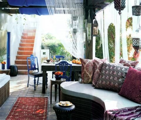 Fantastic deck patio design with cobalt blue painted dining chairs, custom built bench, black leather nailhead ottoman stool and damask and paisley pillows.