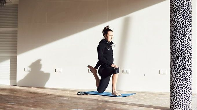 Dani King demonstrates the cycling stretches she does to aid her recovery after a ride.