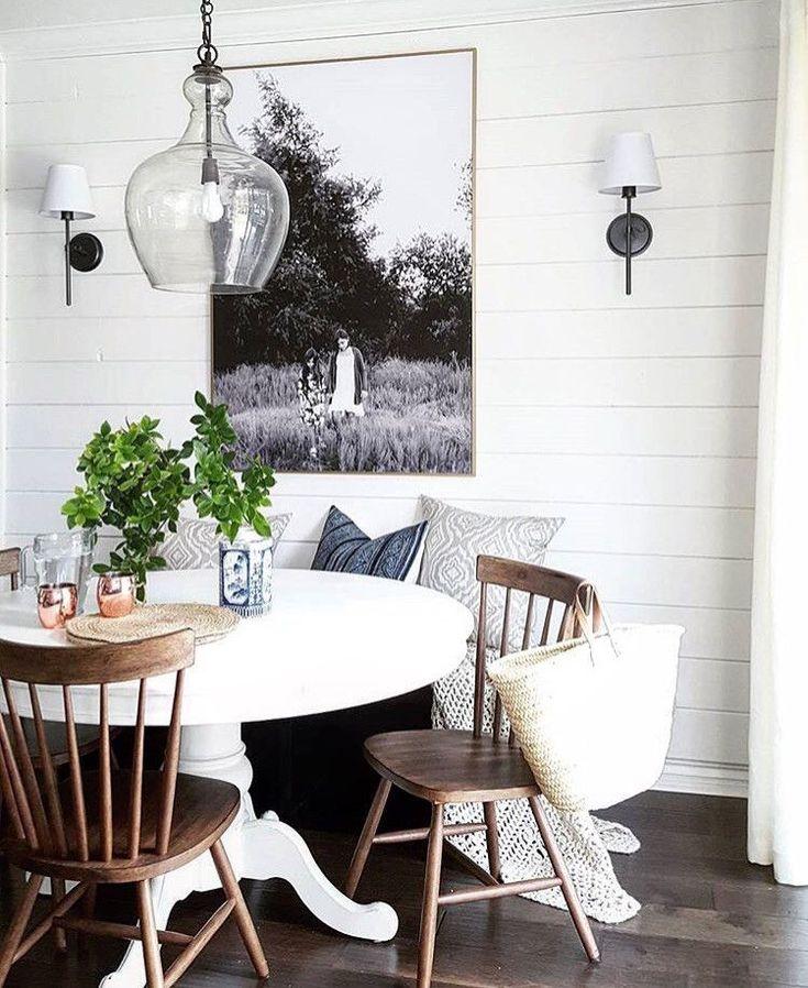 White pedestal table, wood chairs,sconces, b&w art