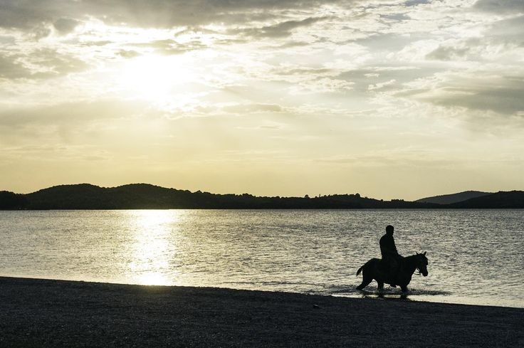 A man is riding away from the reflection of the afternoon sun on the sea. This is the second photo I took of the horse in the sea at the town of Vonitsa.