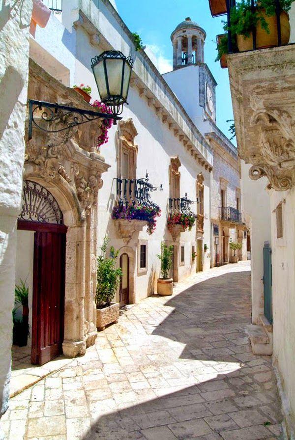 Calle con balcones floridos, paredes blancas , en Locorotondo, Bari, Italia.