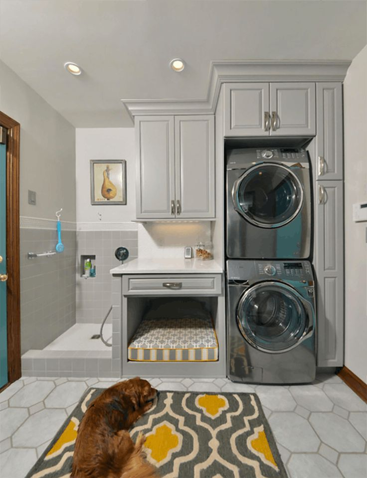 Inspiration for pet friendly remodeling project! A walk-in dog washing station next to cabinets full of pet supplies, as well as a hidden away dog bed helps keep this home clean and pet supplies contained!