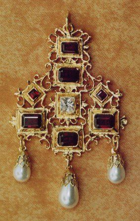 This Garnet Pendant is dated to circa 1600 and was designed by Arnold Lulls, who worked for Anne of Denmark and James I. The central cubic zircon stone is surrounded by Garnets. The original would have been set entirely with table-cut diamonds.