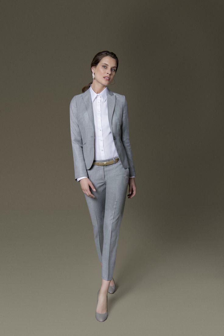 Er wirkt selbstbewusst und streckt die Silhouette: der graue Hosenanzug mit schmal geschnittener Hose. Feminine Highlights wie Pumps und eine weiße Bluse nehmen dem Dandy-Look die maskuline Strenge.