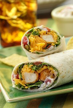Crisp Chicken Tenders Topped With Spicy Sauce Shredded Lettuce And Cheese Wrapped In Warm Tortillas