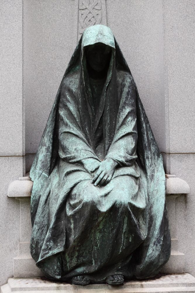 """A visit to Bellefontaine Cemetary would not be complete, too, without a glance at the very spooky figure that looks over the David R. Francis tomb and family plot. Today the dim light completely hid the face."""