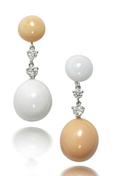 A pair of non-nacreous natural pearl and diamond pendent earrings Composed of an opposing, natural clam and cassis pearl of orange or white hue, linked together by brilliant-cut diamonds, mounted in 18k white gold, diamonds approximately 0.50 carat total, length 3.3cm