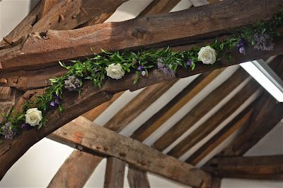 like this - slim garland few simple flowers through it - was thinking of this style of garland for top table could also have this style for church arch