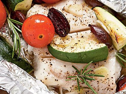 Halibut with Tomatoes, Rosemary, and Zucchini in Foil Packets | Grilling in aluminum foil packages is a practical riff on the French technique en papillote, where ingredients are wrapped in parchment paper and baked. The food steams, making it tender and flavorful. For the grill, use heavyduty foil, or double up the regular kind.