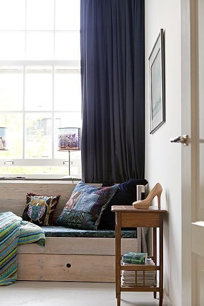 The rich, luxurious, purple fabrics give a soft touch to the rough-looking wooden bench. #curtains