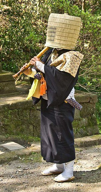 A komuso Buddhist monk in Kamakura, Japan. Komuso monks travelled widely on pilgrimage, hiding their faces under straw hats to help them to achieve humility. They were adherents of Fuke Zen Buddhism, and they used to be a common sight in Japan. They played the shakuhachi flute both as a form of meditation, and to call for alms. Ninja may have disguised themselves as komuso monks so they could travel freely throughout the country without arising suspicion.