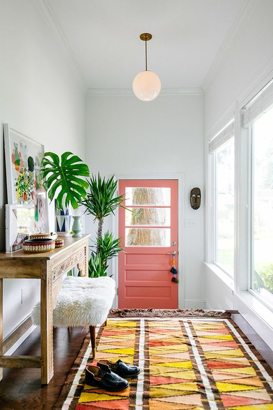 pink door, rug, console table, furry stool, cheese plant