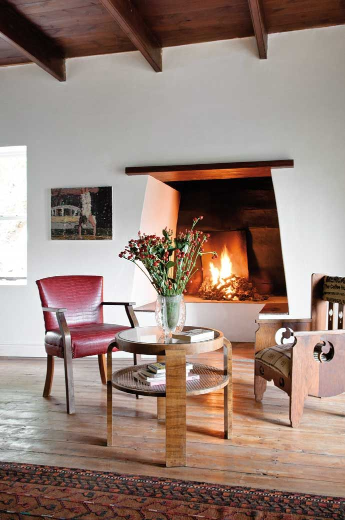 A deep fireplace known as a binnebraai, warms the living room of this Cape Winelands cottage.