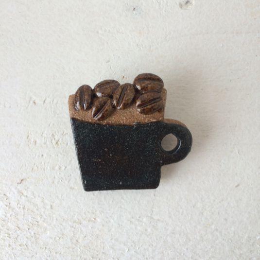 リアルなコーヒー豆とマグカップをモチーフに制作した、陶器のブローチです。一個一個手でカットし、焼き、模様&色付けしているため、 同じものは他にありません。同じ様に作っても焼き縮みなどにより若干サイズが異なりますので、個体差をご理解ください。手作り感の残る歪みや出っ張りのある素朴な仕上がりです。 既製品に見られるカチカチとした印象とは異なります。陶器製ですので、落とすと割れます。およそ5g