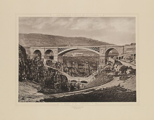 Pont d'El Kantara (El Kantara Bridge)by unknown, 1883, Constantine, Algeria, DeGolyer Library, SMU, from Les Travaux Publics de la France, Tome Premier: Routes et Ponts. 1 photographic print: collotype; 26 x 35 cm on 40 x 56 cm mount. This photograph is one of 50 plates in Public Works of France, Volume One: Roads and Bridges. #bridges #canyons #photographs #collotypes