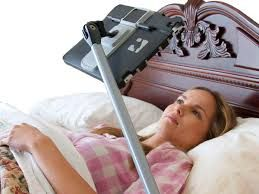 Woman watching movies in bed on iPad using SwingHolder floor stand